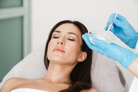 Photo of relaxed caucasian woman getting cosmetic procedure by specialist while lying in beauty salon Stock Photo