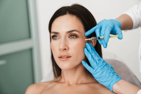 Photo of beautiful woman getting mesotherapy treatment in face by specialist in gloves in beauty salon