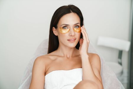 Photo of adult caucasian woman with eyes patches looking at camera while sitting in beauty salon Stock Photo