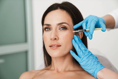 Photo of beautiful woman getting mesotherapy treatment in face by specialist in gloves in beauty salon Stock Photo - 139087735