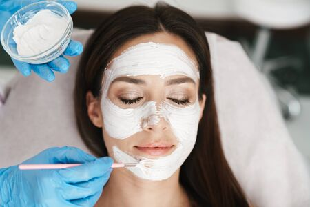 Photo of attractive adult woman getting cosmetic procedure by specialist while lying in beauty salon