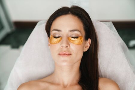 Photo of relaxed caucasian woman getting cosmetic procedure with patches in beauty salon Stock Photo