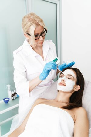 Photo of attractive brunette woman getting cosmetic procedure by specialist while lying in beauty salon