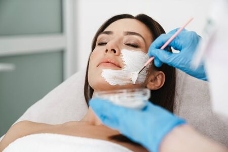 Photo of attractive caucasian woman getting cosmetic procedure by specialist while lying in beauty salon