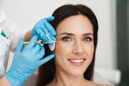 Photo of smiling woman getting mesotherapy treatment in face by specialist in gloves in beauty salon Stock Photo