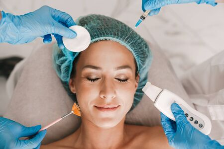Photo closeup of pleased caucasian woman getting cosmetic procedure and injection while lying in beauty salon Stock Photo