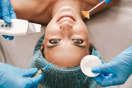 Photo closeup of happy caucasian woman getting cosmetic procedure and injection while lying in beauty salon
