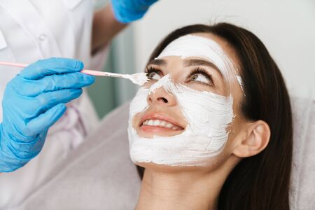 Photo of attractive smiling woman getting cosmetic procedure by specialist while lying in beauty salon