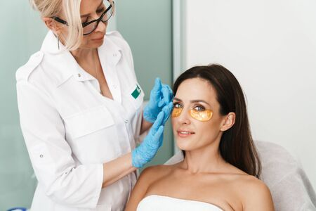 Photo of attractive woman getting cosmetic procedure with patches by specialist in beauty salon