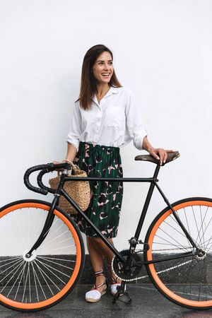 Smiling young brunette woman wearing summer clothes standing at the wall outdoors, holding bicycle, looking away