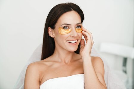 Photo of laughing caucasian woman with eyes patches looking at camera while sitting in beauty salon
