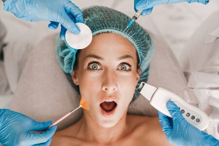 Photo closeup of surprised caucasian woman getting cosmetic procedure and injection while lying in beauty salon