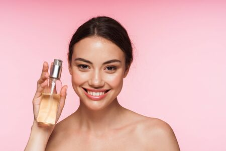 Beauty portrait of a beautiful smiling young topless brunette woman standing isolated over pink background, showing facial oil