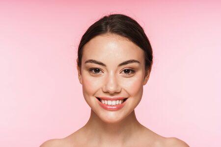 ピンクの背景の上に孤立して立っている美しい笑顔の若いブルネットの女性の美しさの肖像画