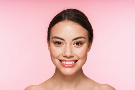 Beauty portrait of a beautiful smiling young brunette woman standing isolated over pink background