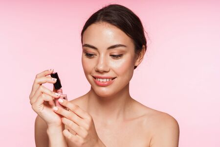 Beauty portrait of a beautiful smiling young topless brunette woman standing isolated over pink background, applying nail polish
