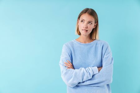 Portrait of a beautiful pensive young blonde short haired woman wearing sweatshirt standing isolated over blue background, holding arms folded Stock fotó