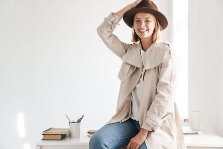 Atrakcyjna uśmiechnięta młoda kobieta w jesiennym płaszczu siedzi w biurze
