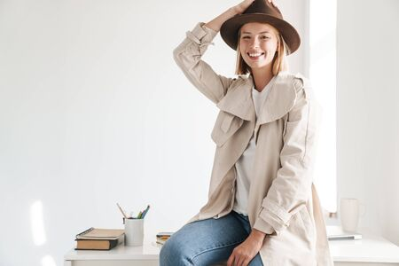 Attraktive lächelnde junge Frau mit Herbstmantel, die im Büro sitzt