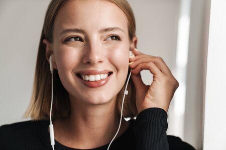 Aantrekkelijke glimlachende jonge blonde kortharige vrouw leunend op een muur terwijl ze binnenshuis staat, luisterend naar muziek met oortelefoons