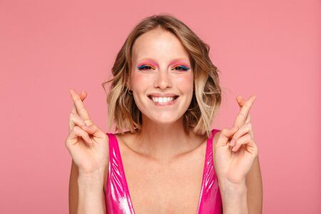 Portrait of a pretty smiling young girl with bright makeup wearing summer clothing standing isolated over pink background, holding fingers crossed for good luck