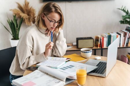 Photo of serious attractive woman making notes in exercise book and using laptop while sitting at table in cozy living room Banco de Imagens