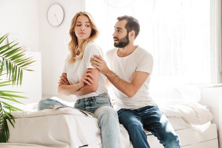 Upset young couple sitting on a couch at the living room, man trying to cheer up his girlfiend