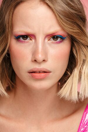 Close up portrait of a beautiful frowning young blonde woman with bright makeup isolated over pink background