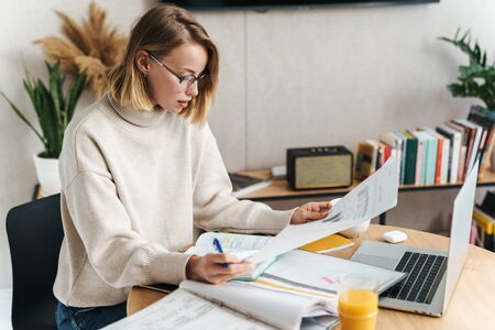 Photo of serious attractive woman examining documents and using laptop while sitting at table in cozy living room Banco de Imagens