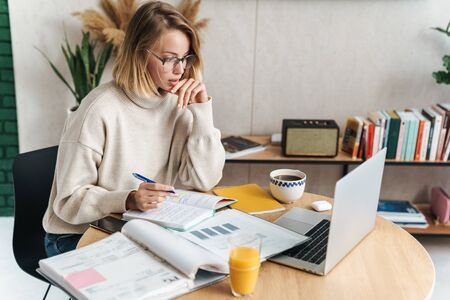 Photo of smart attractive woman making notes in exercise book and using laptop while sitting at table in cozy living room Banco de Imagens