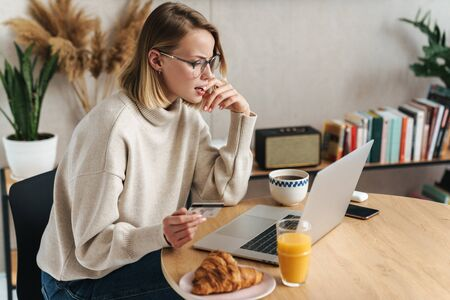 Photo of confused blonde woman holding credit card and using laptop while sitting at table in cozy living room Banco de Imagens