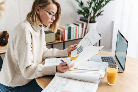 Photo of serious attractive woman examining documents and using laptop while sitting at table in cozy living room Imagens