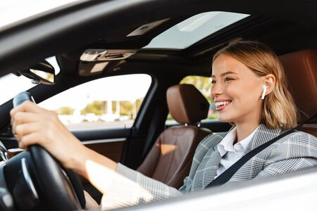 Image of young caucasian successful businesslike woman in formal wear using earbuds while driving car