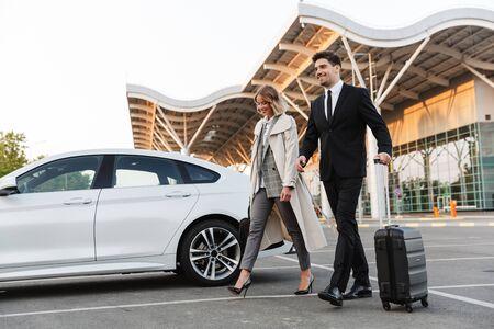 Foto von glücklichen Kollegen, Mann und Frau in formeller Kleidung, die mit Koffer auf dem Parkplatz in der Nähe des Flughafens im Freien spazieren gehen? Standard-Bild