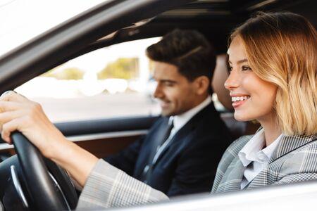 Imagen de joven caucásico exitoso hombre y mujer en ropa formal montando en coche juntos Foto de archivo
