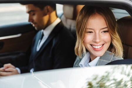 Photo of young blonde businesswoman in formal wear looking at window and smiling while going in car with colleague