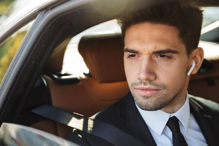 Image of young caucasian successful businesslike man in formal black suit using earbuds while riding in car