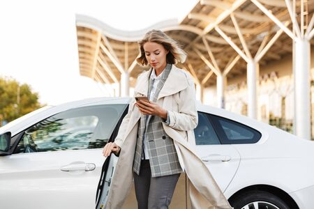 Photo of young businesswoman in formal wear using cellphone while getting out of car on airport parking outdoors