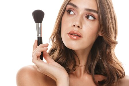 Portrait closeup of caucasian young woman holding makeup brush isolated over white background