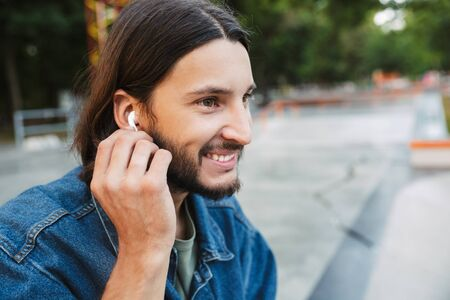 Close up of a smiling brunette hipster man listening to music with wireless earphones while sitting at the skate ramp