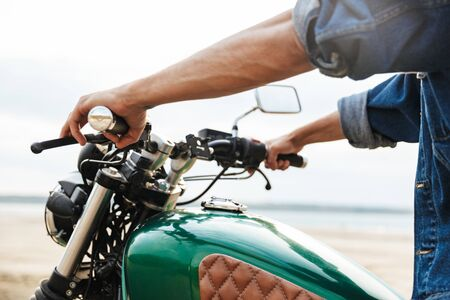 Close up of a man holding handle bars while sitting on a motorcycle at the beach