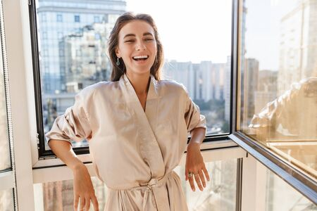 Image of laughing happy amazing young woman indoors posing at home in silk robe near big windows.