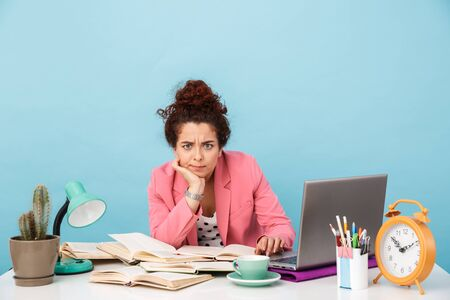 Image of perplexed young woman looking at camera while working at desk isolated over blue background
