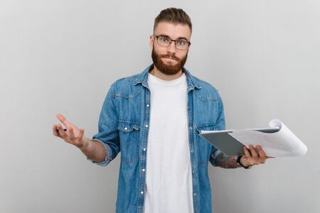 Image of confused handsome man in eyeglasses looking at camera and holding clipboard isolated over gray background Banco de Imagens