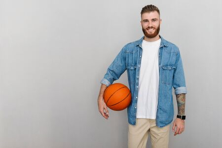 Image of bearded pleased man in denim shirt holding basketball and smiling isolated over gray background