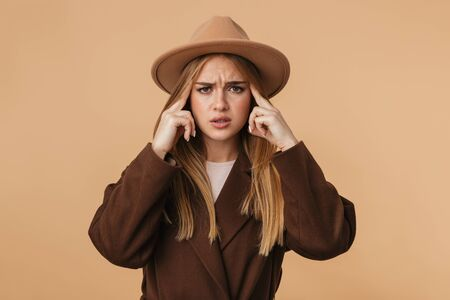 Image of young caucasian girl wearing hat and coat thinking and touching her temples isolated over beige background