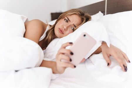 Photo of unhappy caucasian woman with blonde hair using cellphone while lying in bed after sleep
