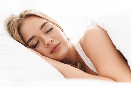 Photo of young caucasian woman with blonde hair sleeping while lying in bed on white pillow