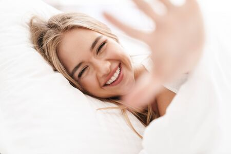 Photo of joyful caucasian woman with blonde hair laughing and looking at camera while lying in bed after sleep