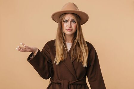 Image of young caucasian girl wearing hat frowing and holding copyspace on her palm isolated over beige background
